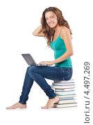 Купить «Студентка с ноутбуком на коленях сидит на стопке книг», фото № 4497269, снято 22 августа 2012 г. (c) Elnur / Фотобанк Лори