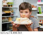 Красивый мальчик ест торт возле открытого холодильника (2013 год). Редакционное фото, фотограф Игорь Низов / Фотобанк Лори