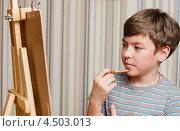 Купить «Задумчивый мальчик-подросток с карандашом стоит перед мольбертом», эксклюзивное фото № 4503013, снято 7 апреля 2013 г. (c) Игорь Низов / Фотобанк Лори