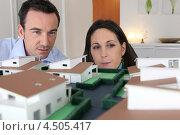 Купить «Муж и жена смотрят на макет жилого комплекса», фото № 4505417, снято 21 января 2010 г. (c) Phovoir Images / Фотобанк Лори