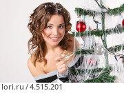 Купить «Девушка в полосатом свитере и искусственным снегом в волосах держит елочный шар на елке», фото № 4515201, снято 24 декабря 2011 г. (c) Losevsky Pavel / Фотобанк Лори