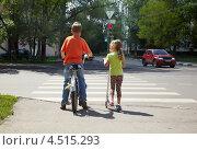 Купить «Двое детей на велосипеде и самокате стоят возле пешеходного перехода», фото № 4515293, снято 18 июля 2011 г. (c) Losevsky Pavel / Фотобанк Лори
