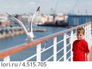 Купить «Мальчик в красной футболке смотрит на чайку, которая ест хлеб на перилах палубы корабля», фото № 4515705, снято 20 июля 2011 г. (c) Losevsky Pavel / Фотобанк Лори