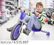 Купить «Счастливый мальчик на трехколесном велосипеде в магазине», фото № 4515897, снято 10 сентября 2011 г. (c) Losevsky Pavel / Фотобанк Лори