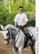 Купить «Жокей в очках с хлыстом на лошади на ипподроме», фото № 4516541, снято 10 июня 2011 г. (c) Losevsky Pavel / Фотобанк Лори