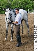 Купить «Жокей возле кормит лошадь с руки на ипподроме», фото № 4516557, снято 10 июня 2011 г. (c) Losevsky Pavel / Фотобанк Лори