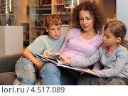 Купить «Мама с двумя детьми на диване читает книгу», фото № 4517089, снято 27 июля 2011 г. (c) Losevsky Pavel / Фотобанк Лори