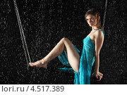 Купить «Молодая женщина в платье на качелях под дождём», фото № 4517389, снято 10 ноября 2011 г. (c) Losevsky Pavel / Фотобанк Лори