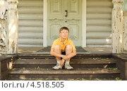 Купить «Мальчик в очках сидит на крыльце деревянного дома», фото № 4518505, снято 3 июля 2011 г. (c) Losevsky Pavel / Фотобанк Лори