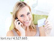 Девушка говорит по мобильному телефону, держа банковскую карту в руках. Стоковое фото, агентство Wavebreak Media / Фотобанк Лори