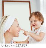 Маленькая девочка мажет нос мамы кремом. Стоковое фото, агентство Wavebreak Media / Фотобанк Лори