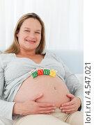 Купить «Радостная беременная женщина выложила на своем животе кубики со словами беби», фото № 4547021, снято 27 октября 2010 г. (c) Wavebreak Media / Фотобанк Лори