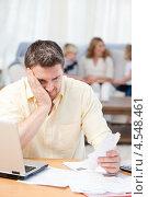 Купить «Удрученный мужчина смотрит на счета. На заднем плане семья сидит на диване», фото № 4548461, снято 26 октября 2010 г. (c) Wavebreak Media / Фотобанк Лори