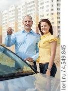Купить «Молодая пара стоит около машины на фоне новых домов. Мужчина держит в руке ключи», фото № 4549845, снято 13 августа 2012 г. (c) Яков Филимонов / Фотобанк Лори