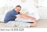 Купить «Пожилой мужчина занимается гимнастикой на полу в домашней обстановке», фото № 4559529, снято 30 октября 2010 г. (c) Wavebreak Media / Фотобанк Лори