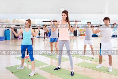 Групповое занятие в фитнес-центре. Молодые люди выполняют упражнение с бодибарами