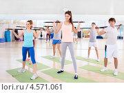 Групповое занятие в фитнес-центре. Молодые люди выполняют упражнение с бодибарами. Стоковое фото, фотограф Raev Denis / Фотобанк Лори