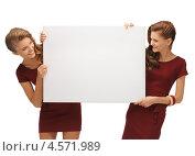 Купить «Две девушки в темно-красных платьях держат чистый баннер на белом фоне», фото № 4571989, снято 28 октября 2012 г. (c) Syda Productions / Фотобанк Лори
