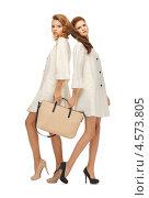 Купить «Две девушки в светлых плащах с большой сумкой», фото № 4573805, снято 28 октября 2012 г. (c) Syda Productions / Фотобанк Лори