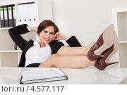 Купить «Эффектная бизнес-леди отдыхает в офисе, положив ноги на стол», фото № 4577117, снято 7 июня 2012 г. (c) Андрей Попов / Фотобанк Лори