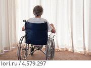 Купить «Вид сзади на пожилую женщину, сидящую в инвалидном кресле перед окном со шторами», фото № 4579297, снято 6 ноября 2010 г. (c) Wavebreak Media / Фотобанк Лори
