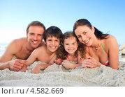 Купить «Семья из четырех человек лежит на песчаном пляже», фото № 4582669, снято 13 ноября 2010 г. (c) Wavebreak Media / Фотобанк Лори