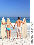 Влюбленная пара стоит на берегу моря с досками для серфинга. Стоковое фото, агентство Wavebreak Media / Фотобанк Лори