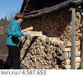 Купить «Женщина складывает дрова в поленницу», фото № 4587653, снято 1 мая 2013 г. (c) EgleKa / Фотобанк Лори
