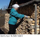 Купить «Женщина складывает дрова в поленницу», фото № 4587661, снято 1 мая 2013 г. (c) EgleKa / Фотобанк Лори