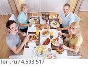 Купить «Дружная семья - отец, мать и взрослые дети обедают вместе за столом», фото № 4593517, снято 17 июня 2012 г. (c) Андрей Попов / Фотобанк Лори