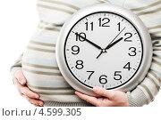 Купить «Беременная женщина держит в руках большие офисные часы, показывающие время», фото № 4599305, снято 14 апреля 2013 г. (c) Илья Андриянов / Фотобанк Лори