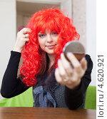 Купить «Девушка примеряет красный парик», фото № 4620921, снято 21 декабря 2012 г. (c) Яков Филимонов / Фотобанк Лори