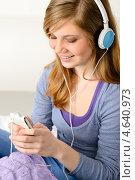 Молодая девушка в наушниках слушает музыку дома. Стоковое фото, фотограф CandyBox Images / Фотобанк Лори