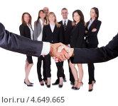 Купить «Деловое рукопожатие на фоне группы бизнесменов», фото № 4649665, снято 12 августа 2012 г. (c) Андрей Попов / Фотобанк Лори