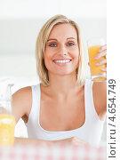Купить «Симпатичная блондинка позирует на камеру со стаканом апельсинового сока», фото № 4654749, снято 29 июня 2011 г. (c) Wavebreak Media / Фотобанк Лори