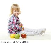 Веселая озорная девочка с яблоками сидит на полу на белом фоне, фото № 4657493, снято 11 марта 2013 г. (c) Мельников Дмитрий / Фотобанк Лори