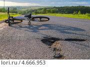 Плохая дорога. Велосипед лежит на загородной дороге. Фокус на дорожной яме. Стоковое фото, фотограф Алексей Попов / Фотобанк Лори