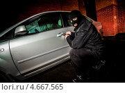 Купить «Автомобильный вор вскрывает дверь у машины.», фото № 4667565, снято 14 ноября 2010 г. (c) Андрей Армягов / Фотобанк Лори