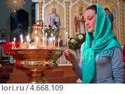 Купить «Девушка ставит свечку в православном храме», фото № 4668109, снято 9 мая 2013 г. (c) Андрей Ярославцев / Фотобанк Лори