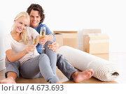 Купить «Счастливая пара празднует новоселье сидя на полу в гостиной», фото № 4673693, снято 14 июля 2011 г. (c) Wavebreak Media / Фотобанк Лори