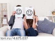 Купить «Пара на диване держит перед лицом смайлики», фото № 4675037, снято 20 октября 2012 г. (c) Андрей Попов / Фотобанк Лори