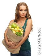 Купить «Девушка держит в руках бумажный пакет с фруктами», фото № 4676665, снято 8 декабря 2012 г. (c) Syda Productions / Фотобанк Лори