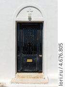 Оригинальная черная старая дверь на белом фоне стены на острове Тира. Санторини, Греция. (2012 год). Стоковое фото, фотограф Галина Вишнякова / Фотобанк Лори