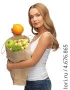 Купить «Девушка держит в руках бумажный пакет с фруктами», фото № 4676865, снято 8 декабря 2012 г. (c) Syda Productions / Фотобанк Лори