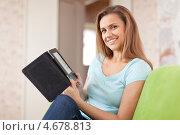 Купить «Улыбающаяся молодая женщина с электронной книгой на диване», фото № 4678813, снято 22 сентября 2012 г. (c) Яков Филимонов / Фотобанк Лори