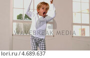Boy in pajamas jumping and shouting in front of window. Стоковое видео, агентство Wavebreak Media / Фотобанк Лори