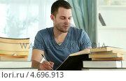 Купить «Writer taking notes while reading books», видеоролик № 4696913, снято 20 октября 2019 г. (c) Wavebreak Media / Фотобанк Лори