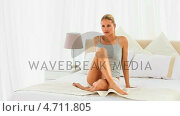Купить «Blonde woman sitting on her bed», видеоролик № 4711805, снято 26 марта 2019 г. (c) Wavebreak Media / Фотобанк Лори