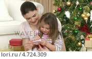 Купить «Close-up of woman and little girl  playing with Christmas presents», видеоролик № 4724309, снято 23 августа 2019 г. (c) Wavebreak Media / Фотобанк Лори