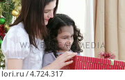 Купить «Close-up of mother and daughter opening Christmas presents», видеоролик № 4724317, снято 22 июля 2019 г. (c) Wavebreak Media / Фотобанк Лори